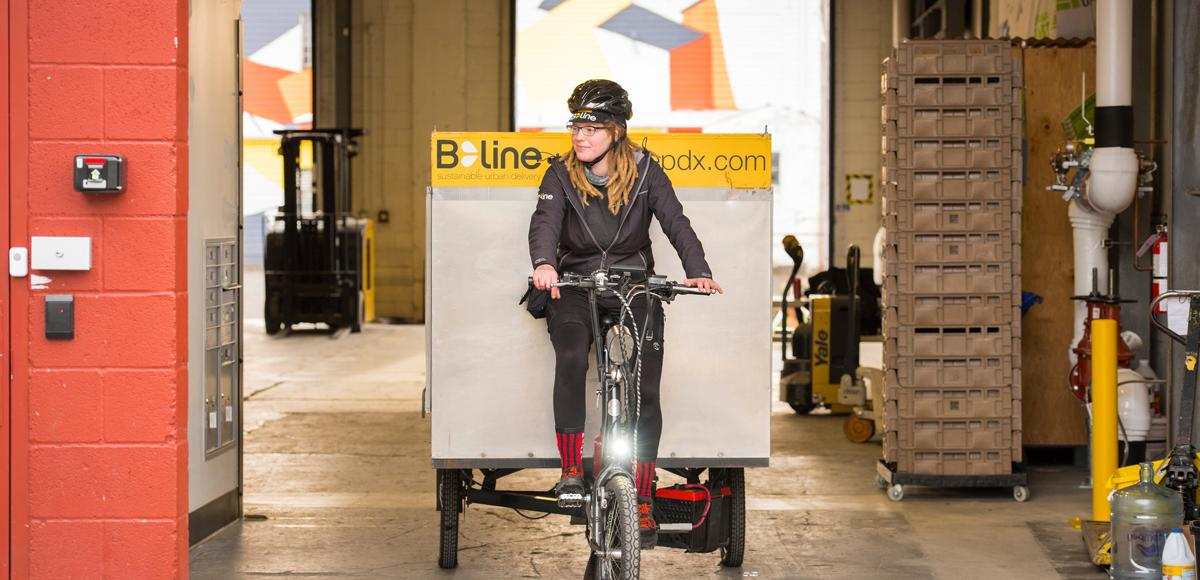 woman rides electric tricycle looking to her right as she exits a warehouse