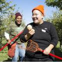 Two women volunteers for the Portland Fruit Tree Project are holding the lacross stick-like batons used to harvest apples. They are gathering the excess bounty in an orchard as part of a harvest party.