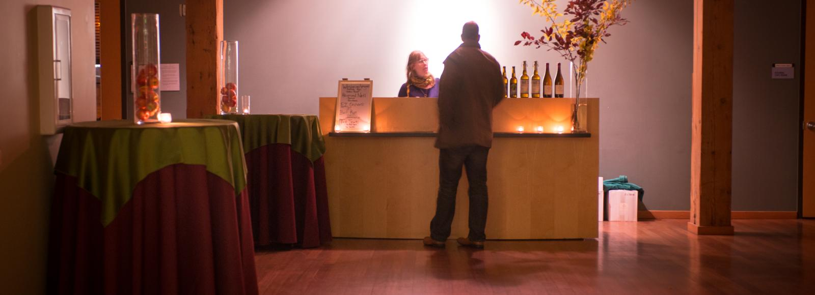 A man orders from the bar at cider stomp in the Ecotrust building