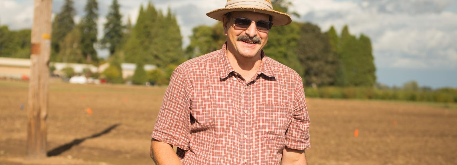 Jim Myers in a field holding a tomato he bred.