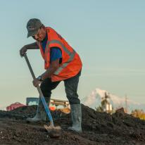 man digging in dirt wearing construction vest, sunset, mountain in background