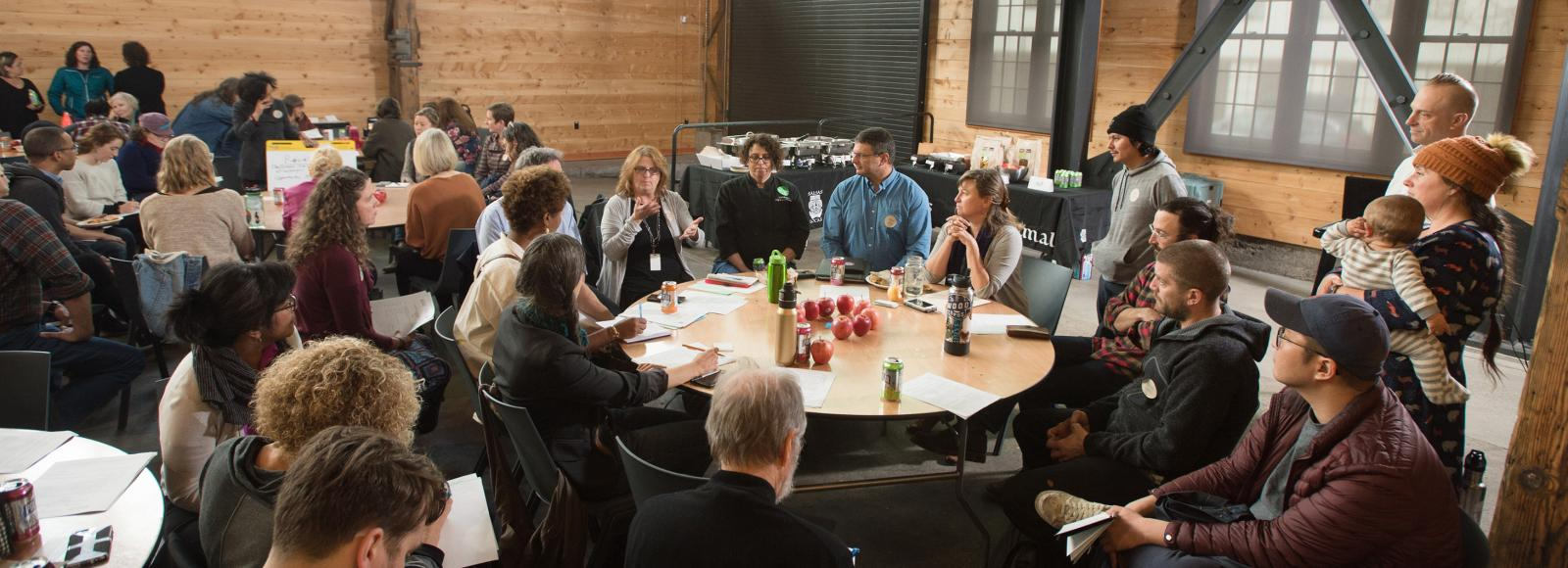 A few dozen people seated around round tables or standing, interacting with each other.