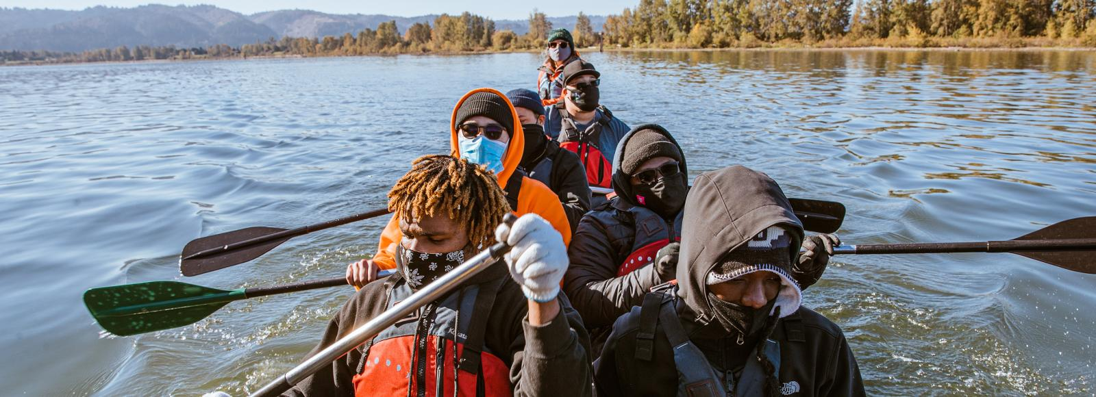 Young adults, all wearing face masks, many of whom are wearing sunglasses, beanies, or hooded jackets, row a canoe together. A tree-lined shore is about a thousand feet behind them.