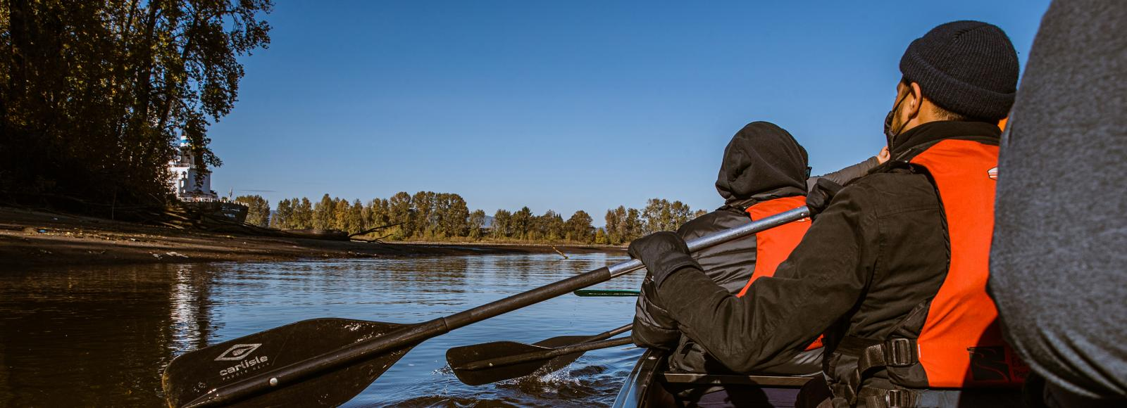 The view of someone's back as they lift an oar over the water. Another person can be seen in front of them, holding an oar in the same position.