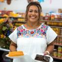 A woman wearing a white blouse with floral embroidery holds two plates of tamales, smiling toward the camera
