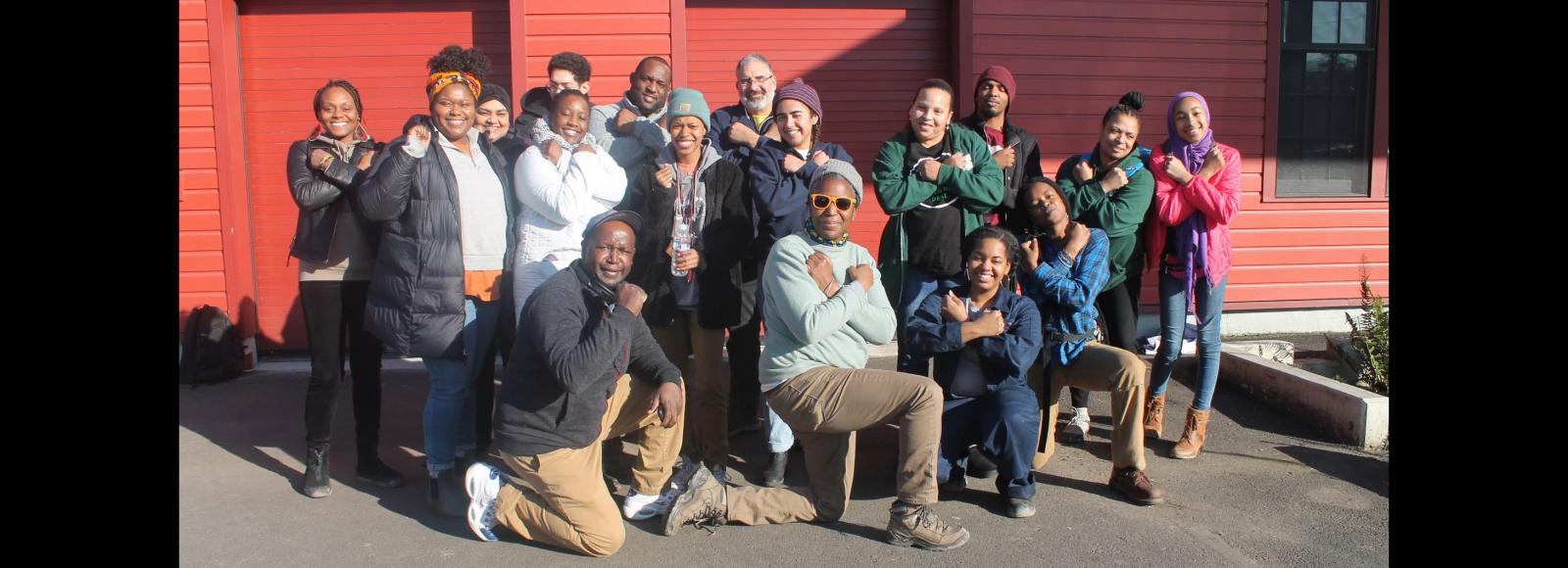 A group of people pose in front of a red warehouse. Some are raising a Black power fist, some are posing with their arms crossed over their chest in the