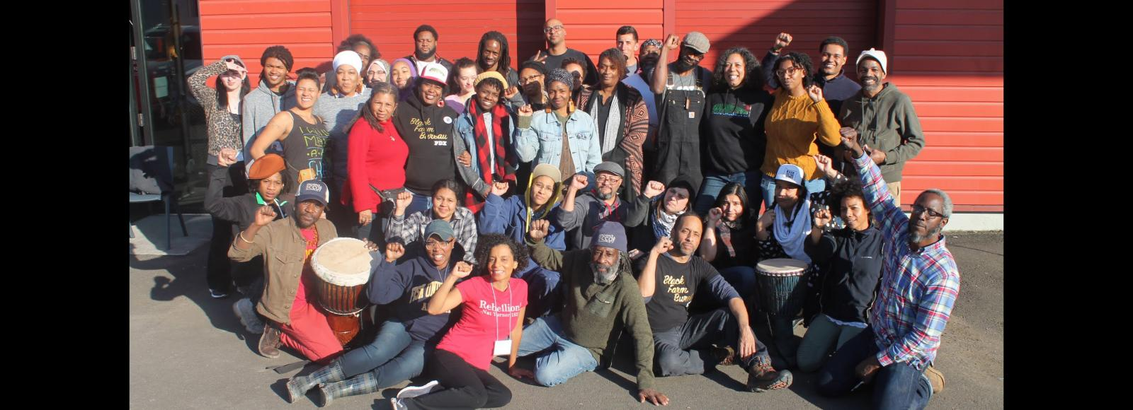 A group of people pose in front of a red warehouse; some folks are raising a Black power fist.