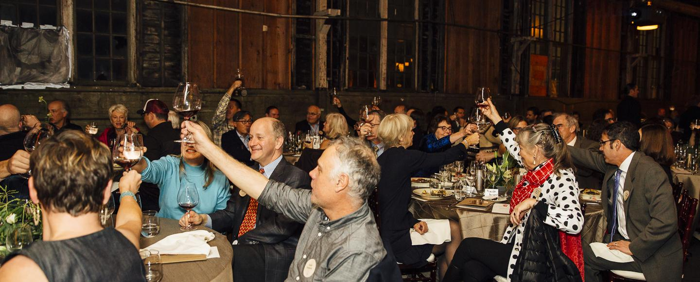 Gala attendees hold up wine glasses and make a toast.