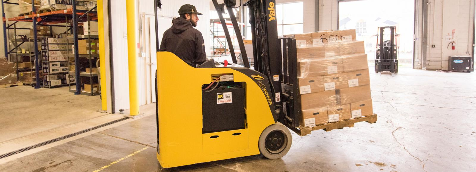A man in black hat and black sweatshirt drives a yellow forklift carrying a stack of boxes.