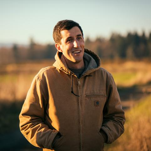 A man in his 30s, with short dark hair and his hands in the pockets of the hooded tan jacket he's wearing, looks smiling to the right of the camera. A grassy field with a line of trees, all cast in sunset light, can be seen behind him.
