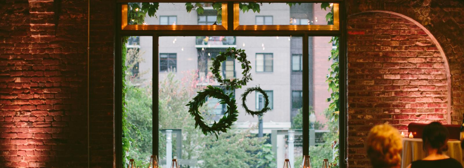 Window with wreaths and candles set up for a wedding ceremony in a historic conference room at the Ecotrust building in downtown Portland