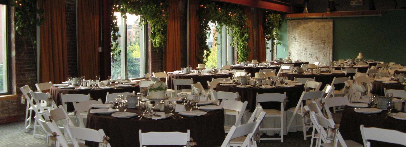 Round tables with formal settings in room with brick walls, windows, and vines