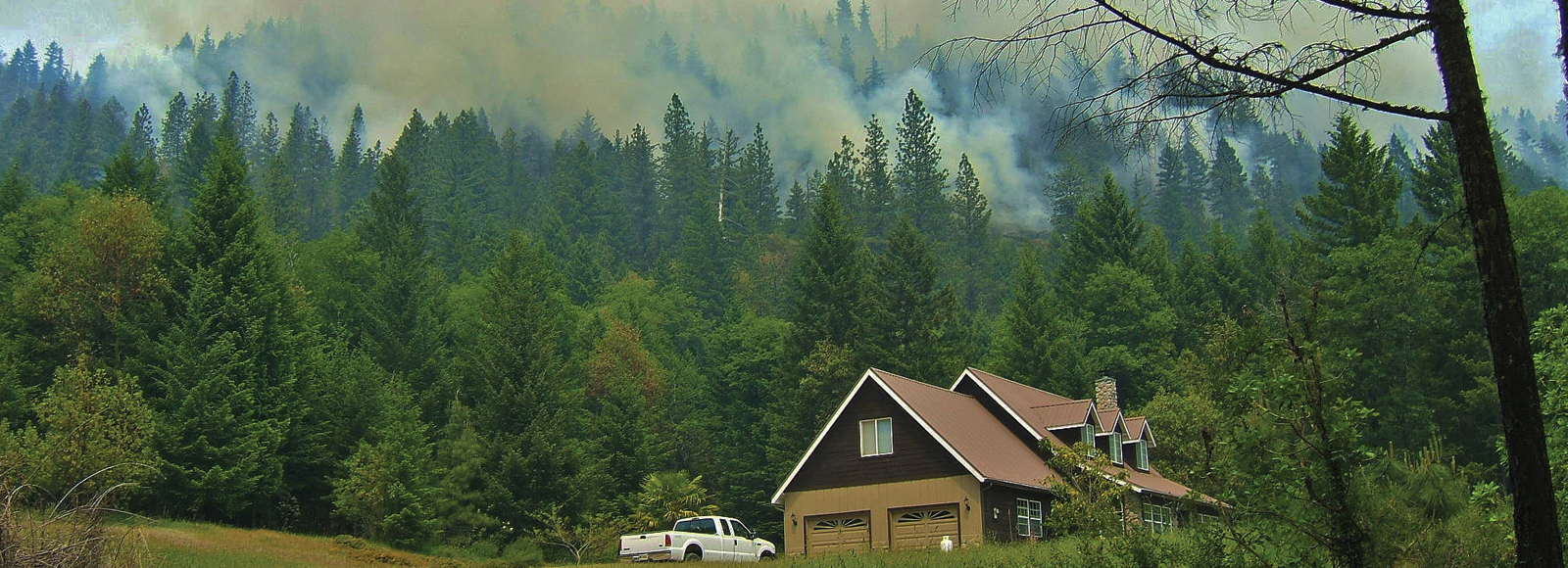 smoke rises from forested hillside above a brown house