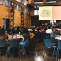 A large group of event attendees gathered around tables in a hall listening to a speaker