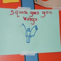 Child's drawing of person with wings that reads: Squash gives you wings