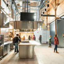 A small tour group examines a stainless steel industrial kitchen