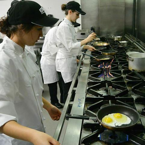 Two competitors cook eggs on a many-burnered range.
