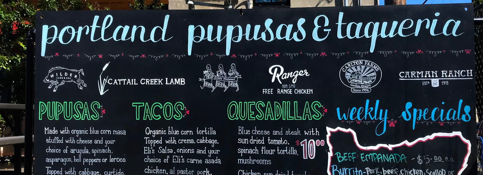 A menu board shows a selection of pupusas, tacos, and quesadillas.