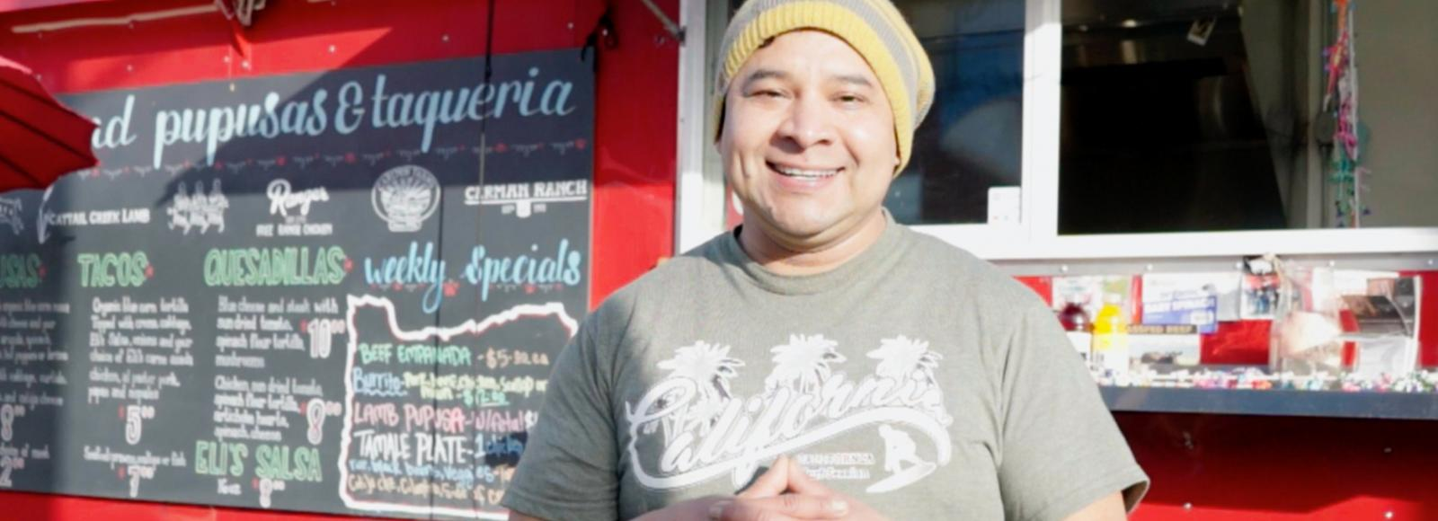 A smiling man stands in front of a red food truck,