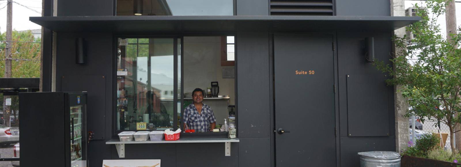 A smiling man stands behind the counter of a small cafe.