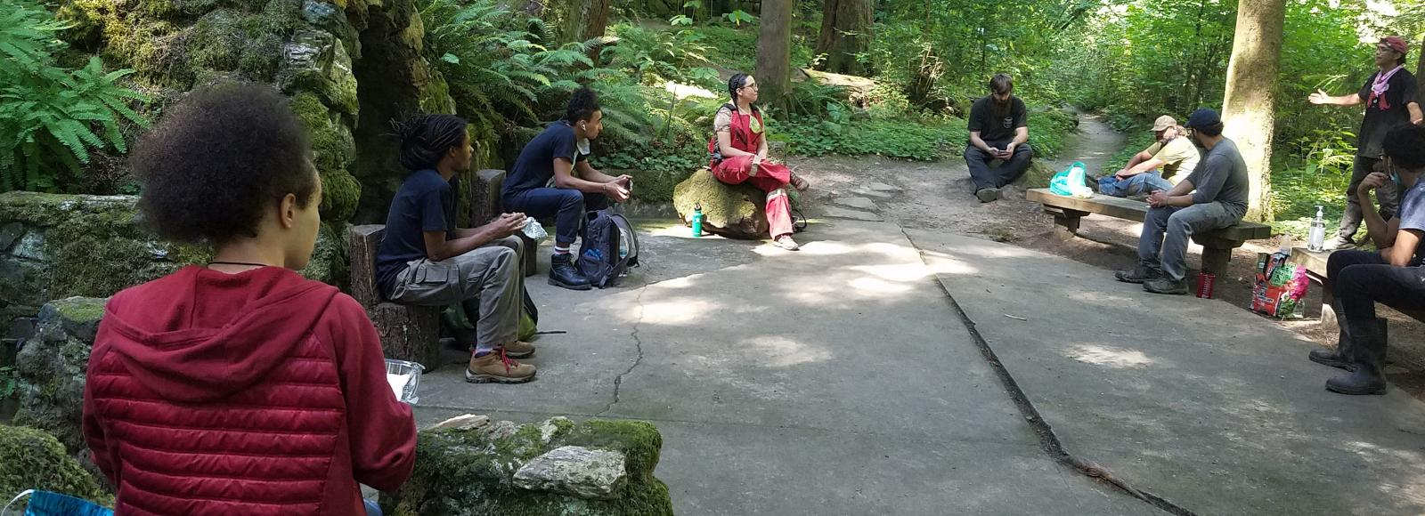 Young adults sit six feet apart. They are looking at a man standing and speaking. They are surrounded by ferns, trees, and dappled sunshine.