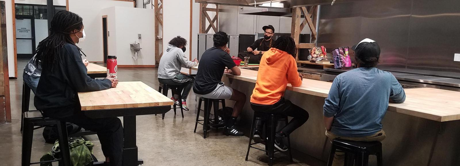 Young adults, sitting six feet apart, gather around a small industrial kitchen counter, while a chef behind the counter talks to them.
