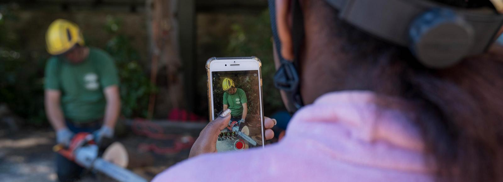A young woman of color wearing a hard hat uses a smart phone to photograph another person demonstrating urban tree care.
