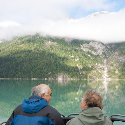 Two men stand on a boat looking out at a river and the mountains beyond