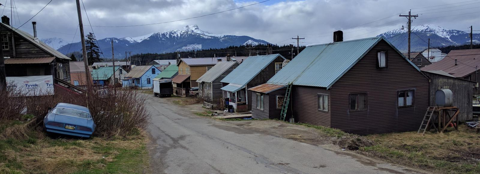 small houses and a blue broken down car line a one-lane paved road