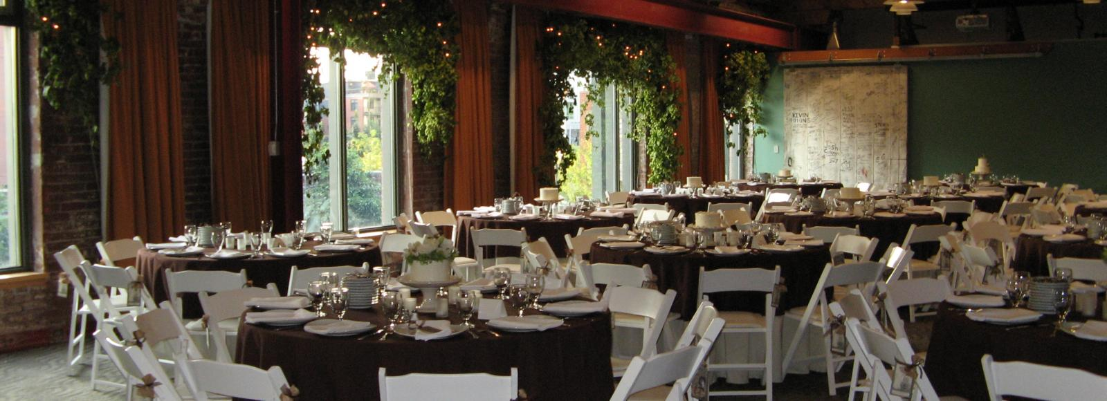 Conference room set up with 20 white tables and chairs, flowers for formal banquet dinner event