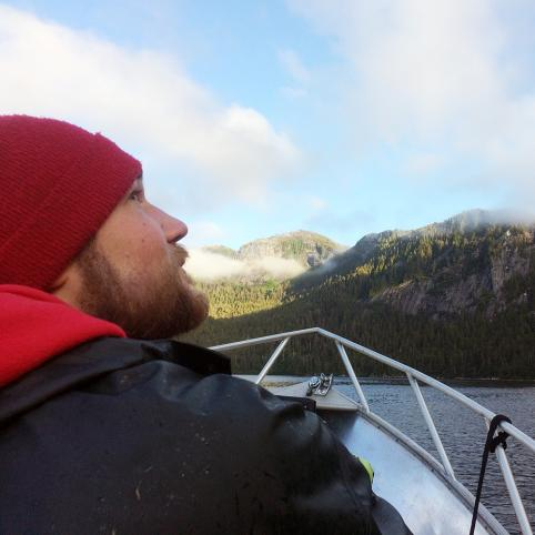 A man with a short beard and red beanie, wearing a heavy black rain coat, glances up ward at the sky. He is sitting near the bow of a small boat. He is surrounded by water and forested hills in the background.