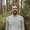 A man with a short beard and wearing a gray long-sleeved T-shirt smiles facing the camera. He is surrounded by conifer trees.