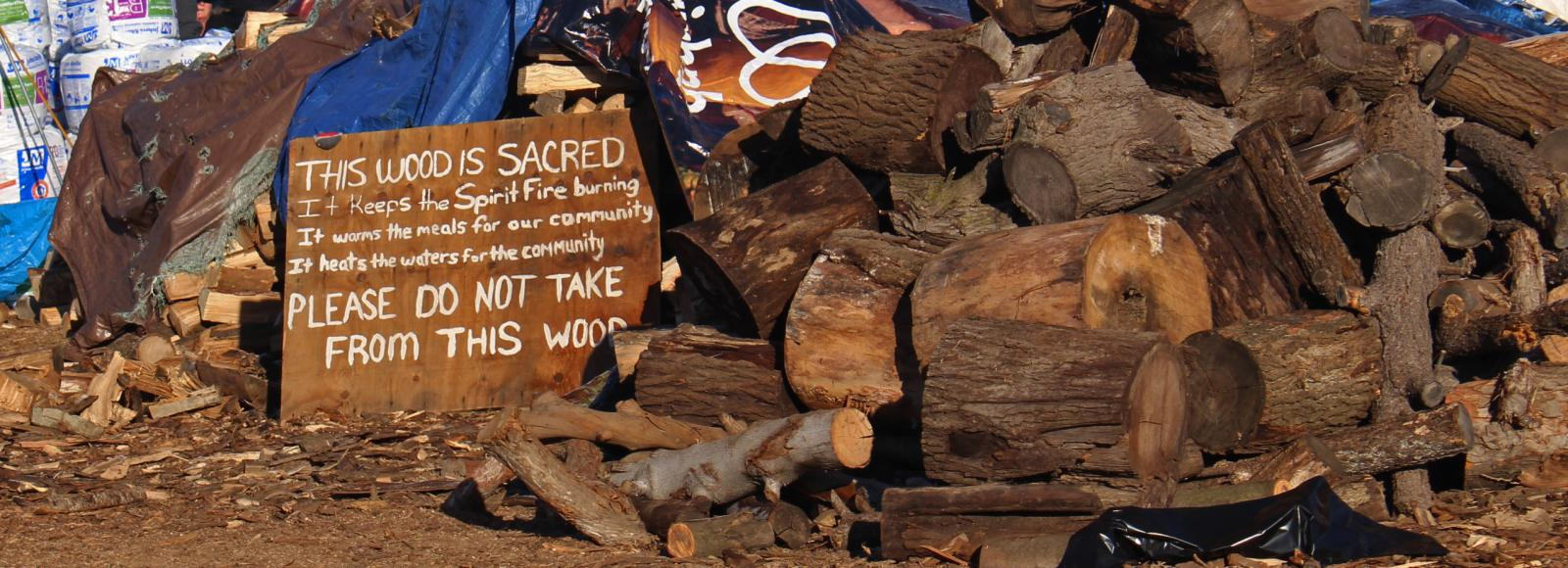 large firewood pile with sign stating