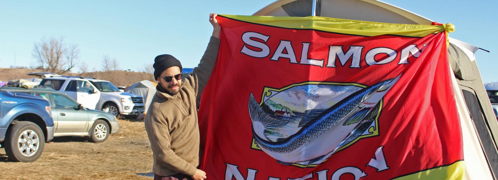 man poses with red Salmon Nation flag in front of tent