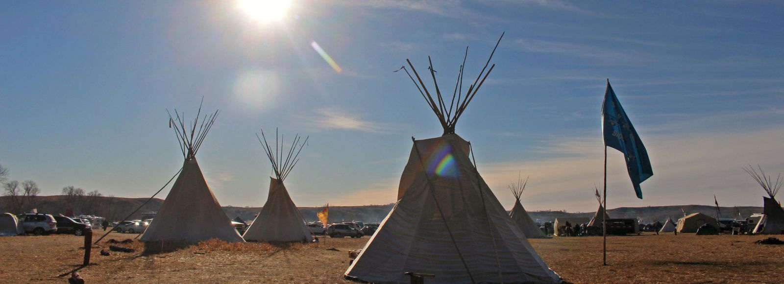 several tipis stand in the sunshine on the plains with blue sky
