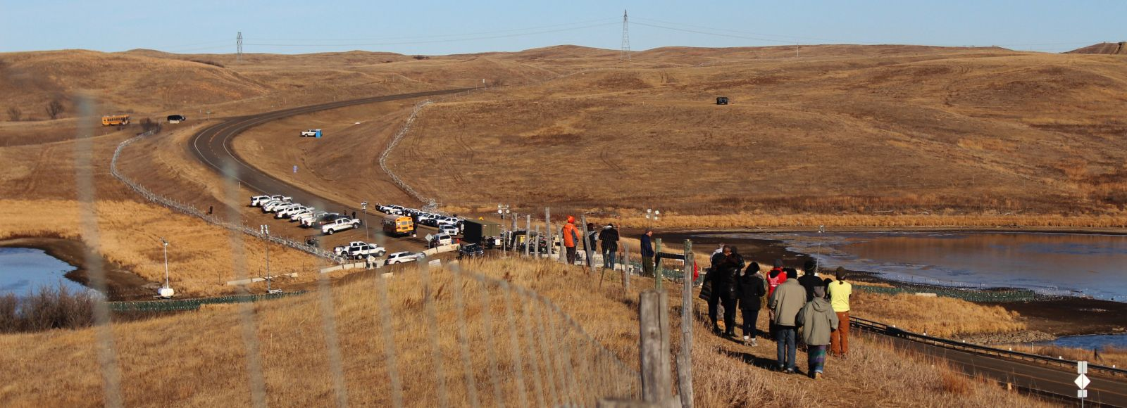 people walk along a fence in the northern great plains
