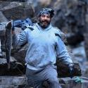 A man with a short, graying beard holds up a just-caught salmon in his right hand, with a slight smile toward the camera. He is wearing a gray hoodie and black bandana on his head. He's surrounded by rocky crags.
