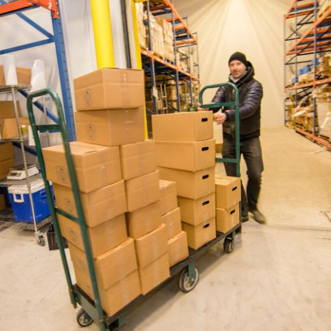 A man in a black jacket and beanie wheels a stack of boxes into a room.