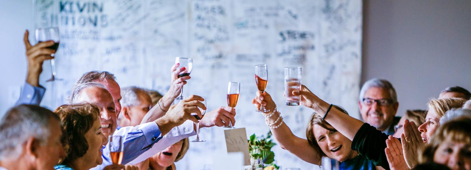 friends and family cheers to newlyweds in the Ecotrust conference room in Portland, Oregon