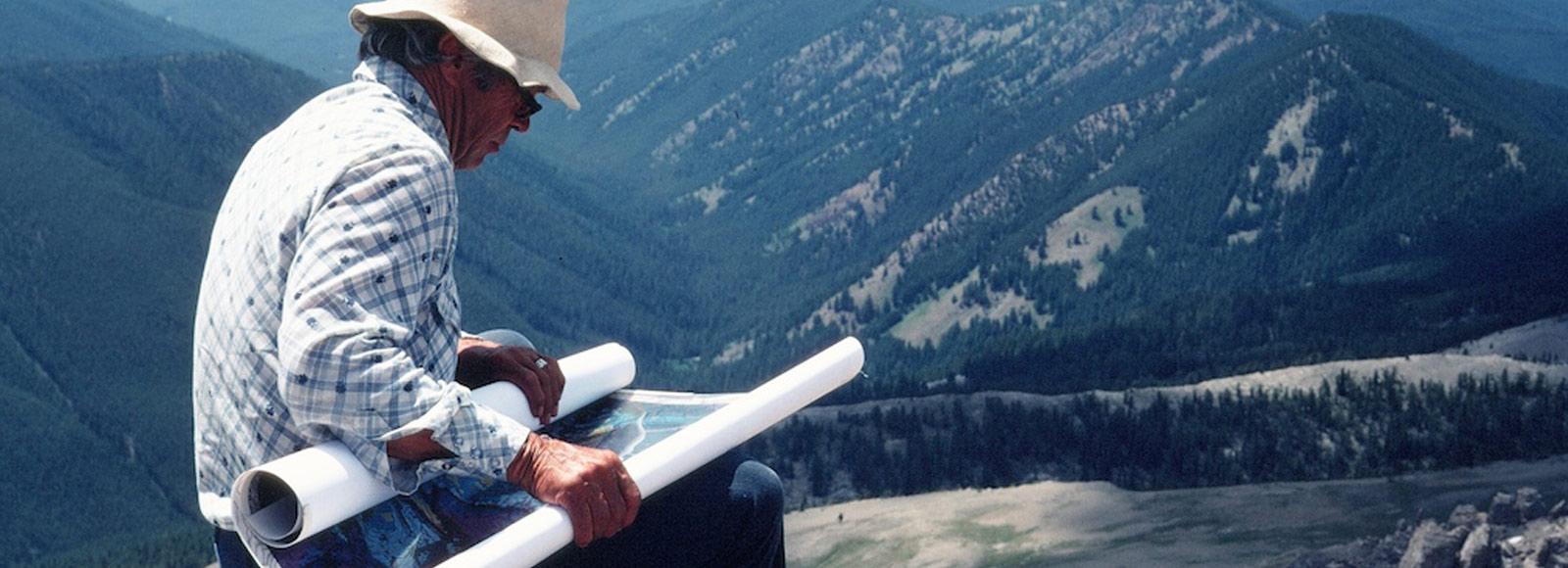 historical image of man in white hat looking at partially rolled map on sunny day on top of mountain