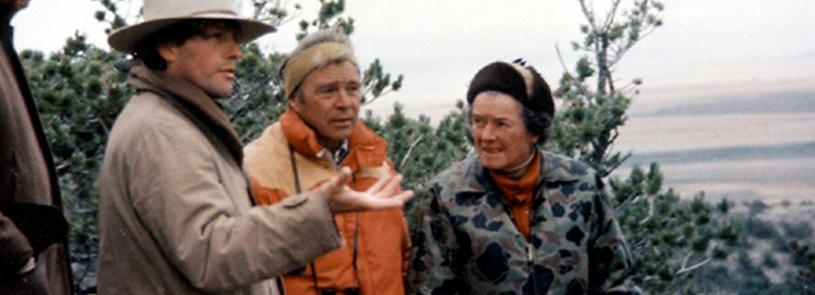 A man in hat, another man in orange vest and a woman in floral jacket and fur hat stand on top of a mountain