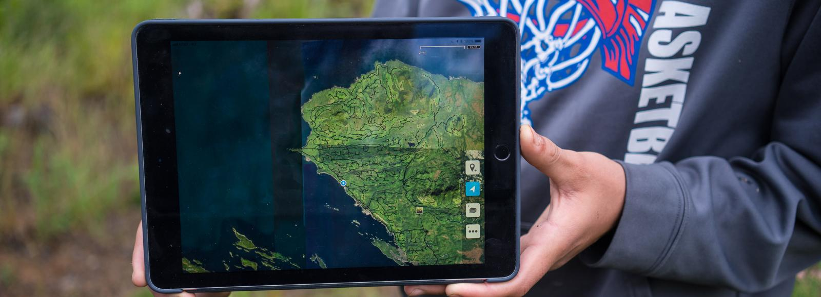 Screen of an electronic tablet, held by a person out of the picture, showing a green map of a peninsula.
