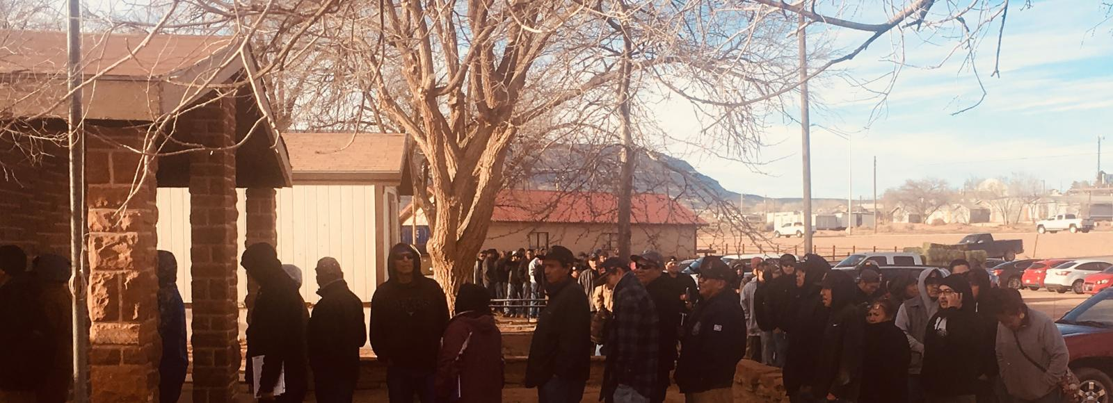 A long queue of adults, mostly men, extends from a small building into a parking lot. Many are wearing hoodies, jackets, and beanies or caps. The line wraps around a large leafless tree.