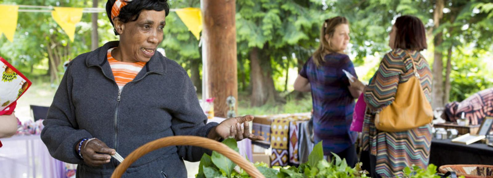 Woman wearing orange headband, grey sweater, and orange shirt gestures to an unseen person from behind a table of greens in a farmers market setting.
