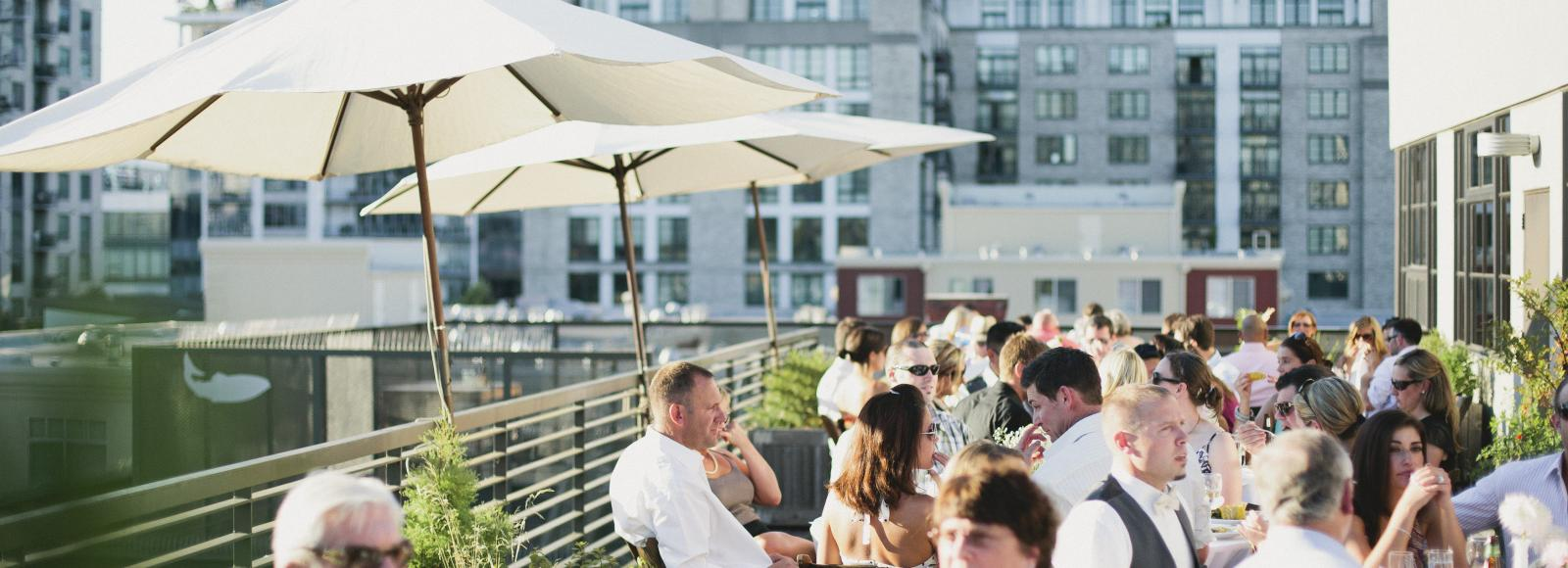 Wedding guests recline at dinner tables on the Ecotrust rooftop terrace. The sun is shining and umbrellas are erected for shade.