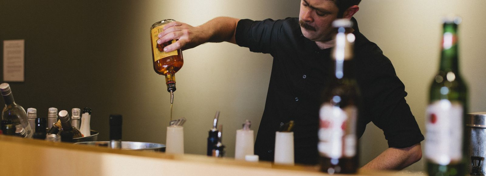 Bartender pours a drink at an Ecotrust wedding