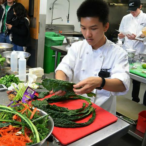 Ngyen inspects leaves of lacinato kale in preparation for the salad phase of the competition.