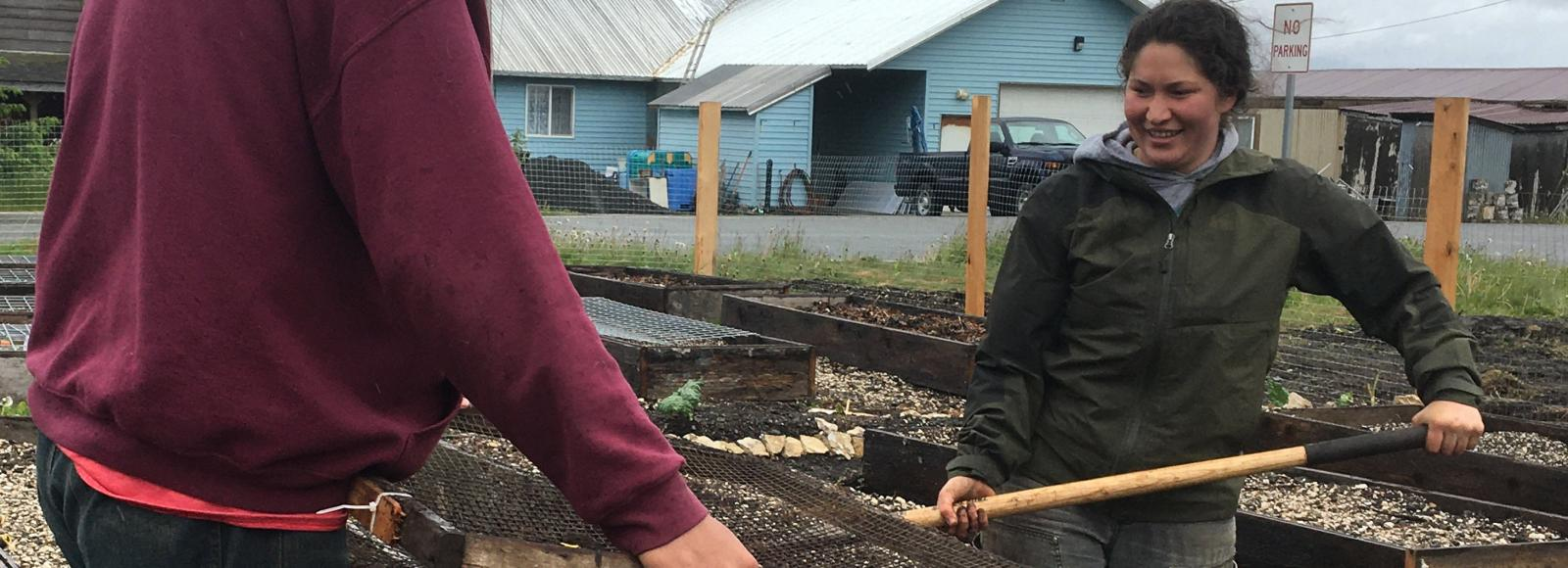 A smiling woman shovels dirt into a sift near some raised garden beds.