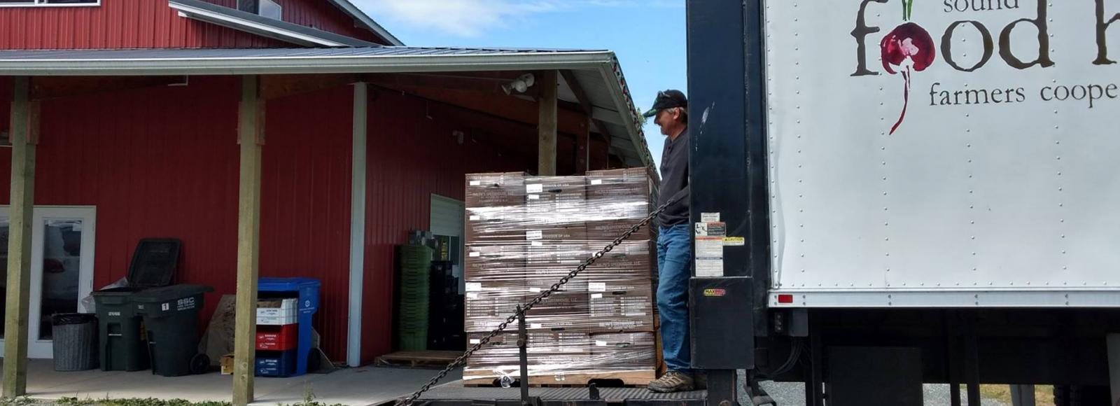 Man in baseball cap, dark shirt, and jeans stands on a distribution truck ramp, lowering a pallet of product.
