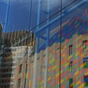 Reflection on glass building with multicolor painting behind